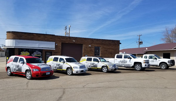 Exterior of LAMB Labor Services staffing agency and warehouse facility in Paynesville, MN with all their company vehicles parked in a row